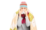 Infected woman covered with blanket blowing her nose in tissue p